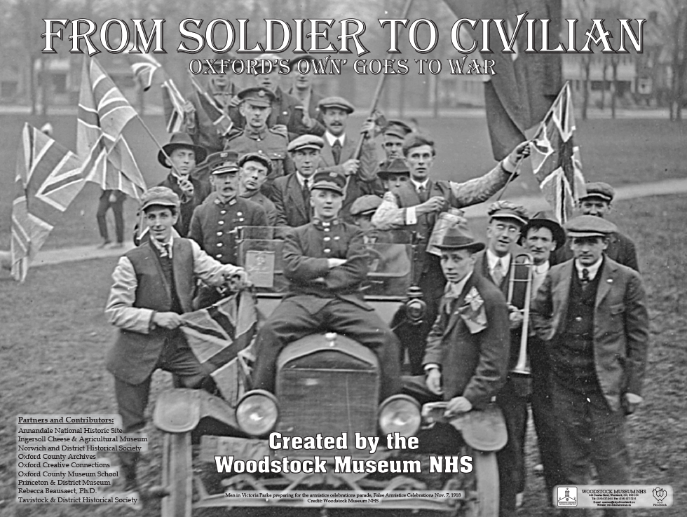 Black and white photo of a group of 20 soldiers gathered around an old car waving British flags