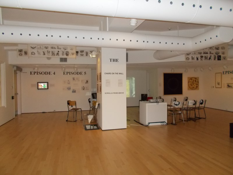 Artworks hanging on the wall in a gallery with chairs in the centre of the room