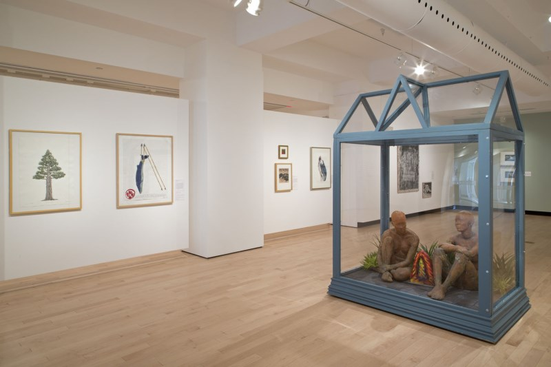 Art gallery space with artwork hanging on the walls and a glass house with two human figures in the middle of the room