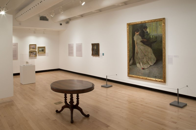 Art gallery space with artwork hanging on the walls and a round wooden table in the centre of the room
