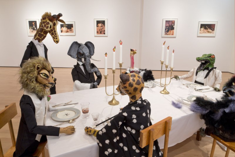 An installation of animal sculptures dressed in formal wear seated around a dinner table